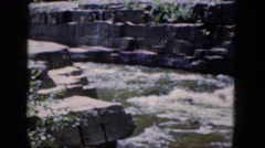 1964: a roaring river flows between rocks topped with grass and trees  Stock Footage