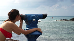 Young woman looking through a coin operated binoculars. Stock Footage