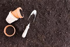 Three small clay pots beside spade in dirt Stock Photos