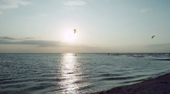 Kitesurfing. Dark silhouettes of surfers riding on boards at dusk. Azov sea. HD Stock Footage