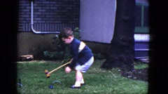 1964: young boy plays croquet by himself in yard near corner of house and tree Stock Footage