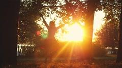 Joyful girl spinning around in autumn park during sunset on sunshine background Stock Footage