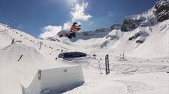 Two snowboarders jump from springboard make full flip in air. Landscape of snowy Stock Footage