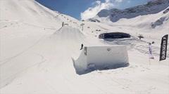 Snowboarder jump on springboard. Landscape of snowy mountains. Blue sky. Ski Stock Footage