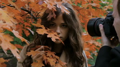 Photographer photographing model among the trees in the park, slow motion Stock Footage