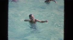 1965: young man swimming past girls in a clear blue public pool CALIFORNIA Stock Footage