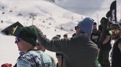 Man speak in microphone. Ski resort. Boy in reflected sunglasses look in camera Stock Footage