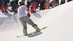 Snowboarder ride on springboard throw ball in basketball basket. Sun. Ski resort Stock Footage