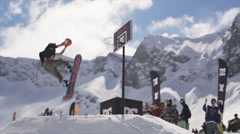 Snowboarder ride on springboard throw ball in basketball basket. Audience. Sport Stock Footage