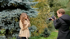 Photographer photographing model among the trees in the park Stock Footage
