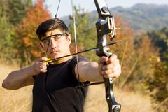 Archer drawing his compound bow trees Stock Photos