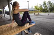 Sporty Young Woman Sitting On Wooden Bench At Park Stock Photos