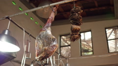 Hanging meat curing in a loft style restaurant space Stock Footage