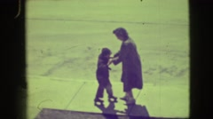 1945: mother is training her child to skating on the ground NEW YORK Stock Footage