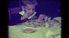 1946: boy at dinner table eating then smiling at the camera and laughing Stock Footage