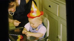 1964: a mother tending to a birthday boy wearing a party hat  Stock Footage