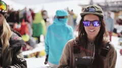 Girls in reflected sunglasses, cap wave head at ski resort in mountains. People Stock Footage