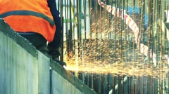 Builder worker cuts rebar with a angle grinder, slow motion Stock Footage