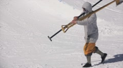 Man walk with two shovels on shoulders. Mountains. Ski resort. Sunny day Stock Footage