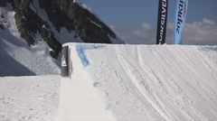 Snowboarder high jump from springboard. Shake board in air. Mountains. Sunny Stock Footage