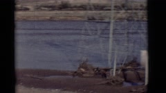 1964: sand water people walking boat on shore windy grey logs cell tower  Stock Footage