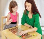 The teacher and the girl at the table studying the cards Stock Photos