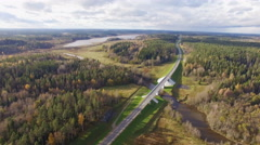 Beautiful aerial view of road bridge over the river surrounded by forest Stock Footage