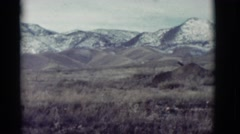 1964: grassy field sits at the base of snow covered mountains on a cloudy day Stock Footage