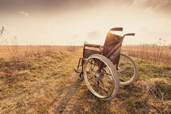 Empty wheelchair on the meadow at sunset - vintage retro version Stock Photos
