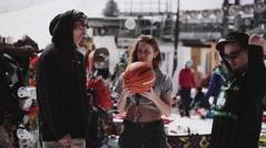 Girl spinning basketball ball on finger with two men. Ski resort. Encamp. Sunny Stock Footage