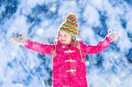 Child having fun in snowy winter park Stock Photos