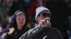Host in blue hat, sunglasses speak in microphone. Ski resort. Encamp. People Stock Footage