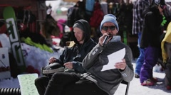 Host in hat, sunglasses speak in microphone. Ski resort. Encamp. Sunny. People Stock Footage