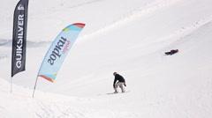 Snowboarder make high jump from springboard, turn around in air. Ski resort Stock Footage