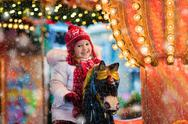 Child riding carousel on Christmas market Stock Photos