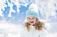 Child having fun in snowy winter park Stock Photos