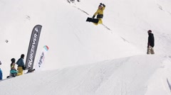 Snowboarder make high jump from springboard, flexes feet in air, turning. Sunny Stock Footage
