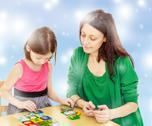 Mom and daughter at the table playing educational games Stock Photos