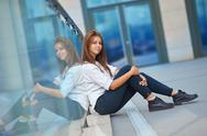 Beautiful young woman sitting near the glass building Stock Photos