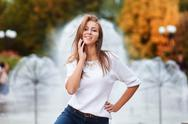 Young beautiful woman walking and posing in city near fountains Stock Photos