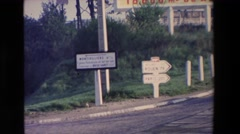 1969: cars pass each other at a cross road marked with several signs to guide Stock Footage