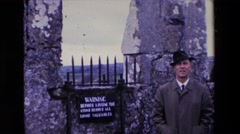 1969: a well dressed man standing in front of a stone fence waving IRELAND Stock Footage