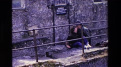 1969: an old man attending a funny lady lying on the ground IRELAND Stock Footage