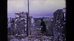 1969: an old woman in black coat walking on a stony structure IRELAND Stock Footage