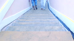 People going up and down the stairs in a narrow alley clear day Stock Footage