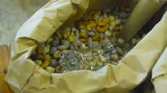 Cashew nuts and almonds in a paper bag on a market stall, a top view Stock Footage