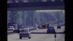 1969: personal and commercial automobiles cruise past an ornate building  Stock Footage
