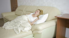 Woman with abdominal pain lying on the sofa. Girl drinking pills painkiller Stock Footage