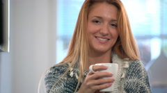 Happy woman drinking coffee in the kitchen and smiling at the camera. Stock Footage