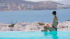 Beautiful young girl relaxing in the edge of swimming pool outdoors with Stock Footage